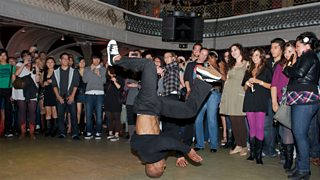 A breakdancer spins upside down on his head
