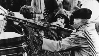 A member of the Provisional Irish Republican Army manning a submachine gun at a roadblock at Londonderry, Northern Ireland, during a march commemorating the events of Bloody Sunday (1978)