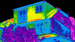 A thermal scanned image of a house losing heat from windows.