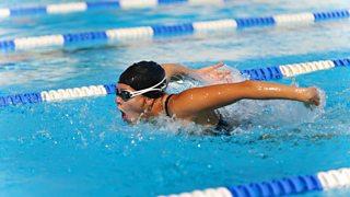 Swimmer doing butterfly stroke in a pool.