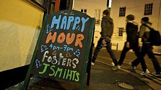 Sandwich board advertising happy hour at a pub