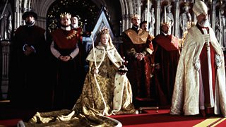 The Queen sits at her thrown in luxurious silks and furs and a glistening crown on her head, surrounded by men