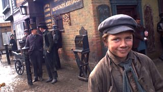 A street boy smiles in the foreground, his period costume torn and dirty and juxtaposed to the business men behind him who wear pristine suites.