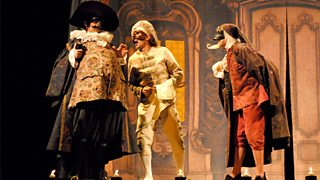 Three males stand on stage in highly-decorated costumes and masks that are indicative of commedia dell'arte.