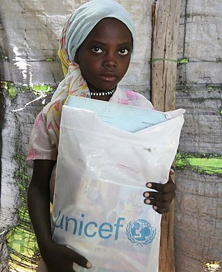 A child holding a bag of items donated by Unicef