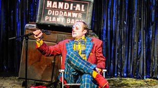 Owen Arwyn mewn gwisg clown yn eistedd mewn cadair yng nghynhyrchiad Pridd gan Aled Jones Williams
