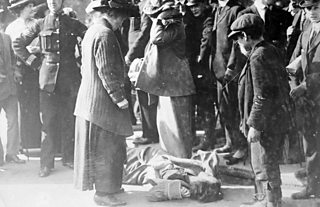 A suffragette lies on the ground as police and bystanders look on