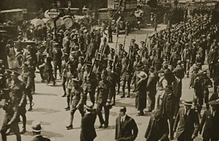 Marching soldiers on parade through a peacetime street