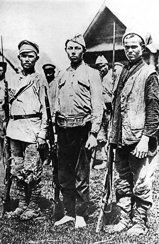 Three Bolshevik soldiers in 1917 dressed in ragged clothing and no proper shoes. Each holds a rifle.