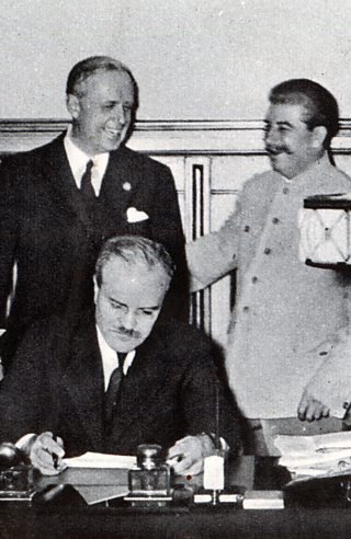 Stalin and von Ribbentrop share a joke as Molotov signs document