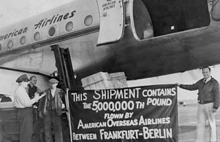 """American Airlines cargo plane with four men beside it. Two hold a banner saying """"This shipment contains the 5,000,000th pound flown by American Overseas Airlines between Frankfurt - Berlin""""."""