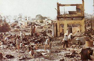 Civilians sorting through rubble of badly damaged buildings