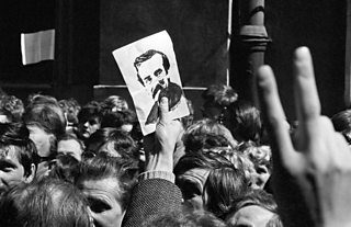 Crowd of people, one of whom holds image of Lech Walesa aloft