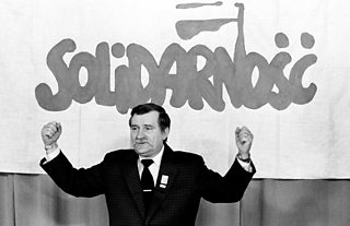"Lech Walesa stands before a ""Solidarity"" banner"