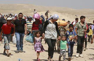 Men, Women and children walking through the desert with all their belongings