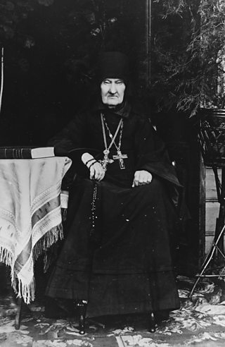 Black-robed man with two large crucifixes around neck