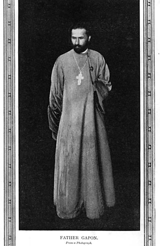 Bearded man in cassock with crucifix around neck