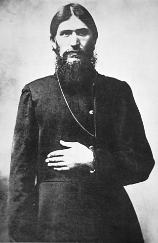 Bearded man with long hair and beard wearing a cassock