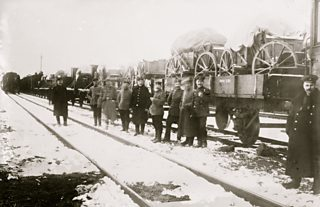 Smiling soldiers in front of railway wagons loaded with artillery pieces