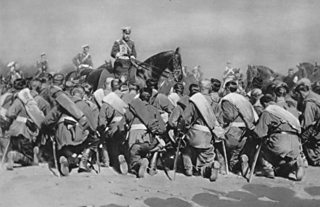 Tsar Nicholas the Second, on horseback holds up religious icon before kneeling soldiers