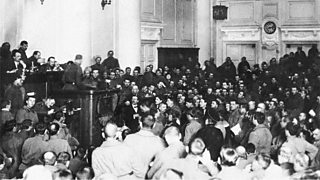 Large room full of men, some uniformed, with attention focussed on a speaker's podium