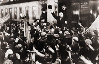 Lenin waves his hat in salute to gathered crowd as he steps down from a railway carriage