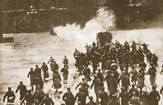Soldiers advance towards a large building