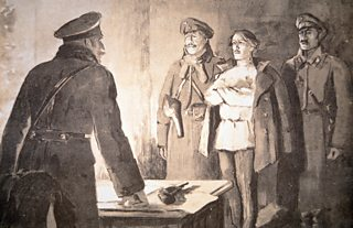 Artist's impression of  man standing with arms folded flanked by two soliders. A Cheka officer, his pistol before him on a desk, asks questions.