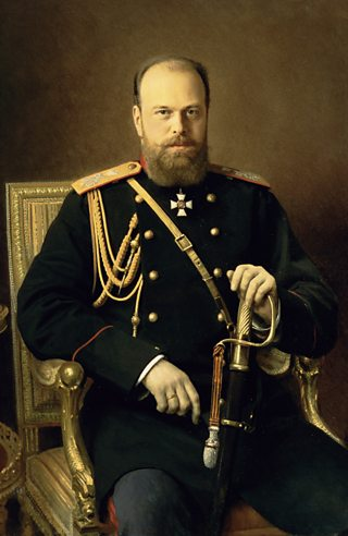 A bearded in man in full dress uniform sits with one hand resting on a sabre