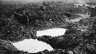 Soldiers crouched at the crater holes of the devastated landscape around Passchendaele Ridge