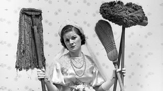 A 1930s bride, sitting beside a bucket, holding a mop and brushes