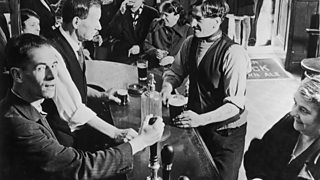 Men and women in a bar in Glasgow in the 1930s. Two children stand in the doorway