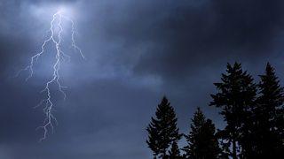 A burst of sliver lightning cracks across a dark stormy sky