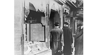 Germans pass by the smashed windows of a Jewish-owned shop in the aftermath of Kristallnacht