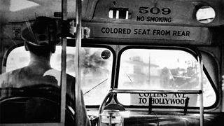 View from behind the back of a bus driver, with a sign on the front of the vehicle that reads 'colored seat from rear.'