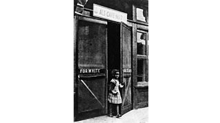 African-American girl leaving a cafe through a door marked 'For Colored' (c. 1950)