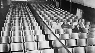 Four men sitting in the half of a cinema reserved for black people only.