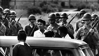 Minnijean Brown, one of the Little Rock Nine, arrives outside Central High School, as members of the 101st Division of the Airborne Command stand ready to protect them.