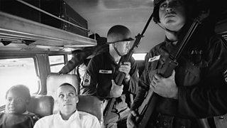 Freedom Riders sitting on board interstate bus as they are escorted by two Mississippi National Guardsmen holding bayonets.