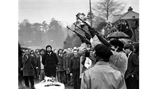 Masked IRA men fire rifle shots over coffin of Bobby Sands en route to the Milltown cemetery, Belfast. Gerry Adams in background. (7th May 1981)