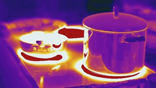 Thermogram of a pan on a stove showing the hottest parts in white, yellow or red, and the coldest parts in purple and black.