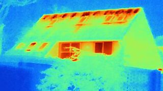 A thermogram of a house, showing areas of heat loss. The roof and the windows are the yellowest and reddest areas, indicating that most energy is lost from the house this way.