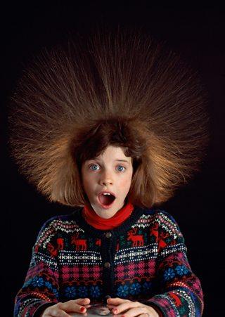 Girl touching Van de Graaff static electricity generator