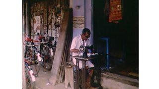 Indian man using antique Singer sewing machine