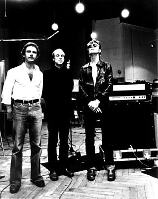 Robert Fripp, Brian Eno and David Bowie pose for a portrait