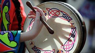 A young Irish girl playing the bodhrun.