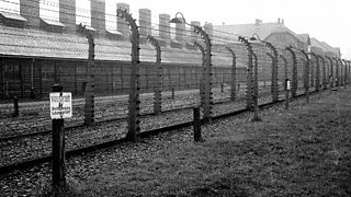 A concentration camp with barbed wire outside.