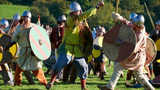 Swordman fighting axeman in a re-enactment of the Battle of Hastings.