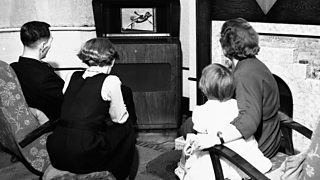 A family sit in front of an old fashioned television in 1950.