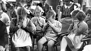 Children clasp their hands and close their eyes to pray.